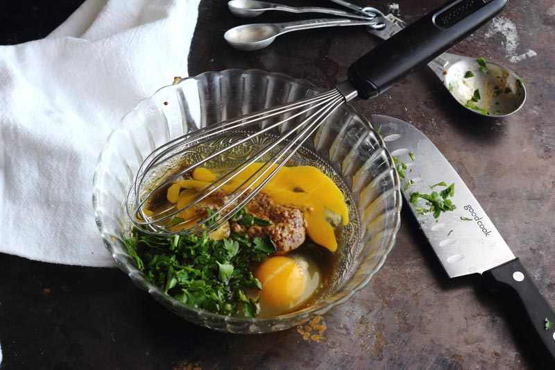 Dill, parsley, stone ground mustard and egg in bowl to be whisked
