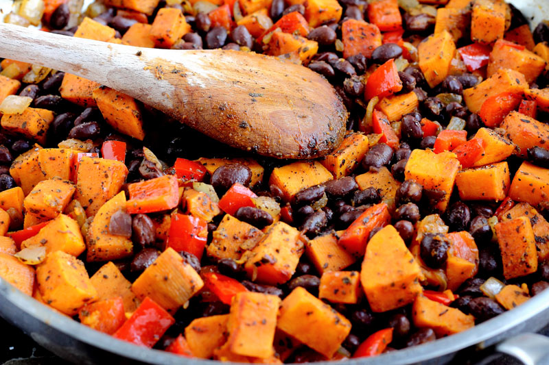 Sweet potato red pepper onion black beans cooking in pan