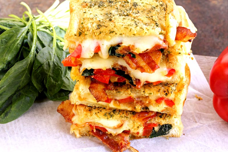 Grilled Cheese with roasted red pepper, crispy bacon, carmelized onions, spinach, pepperjack and mozzarella cheese.