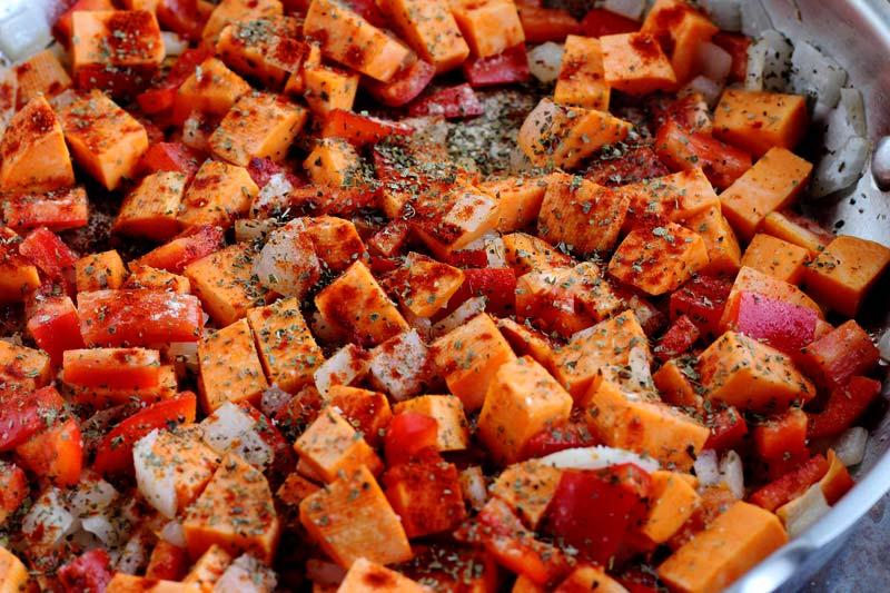 sweet potato red pepper onion seasoned cooking in pan