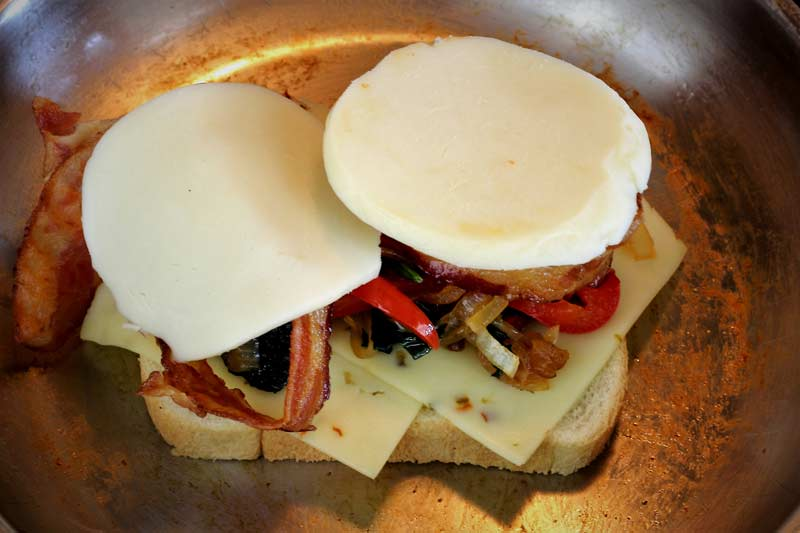 Assembly of grilled cheese pepper jack roasted red pepper caramelized onion spinach bacon and mozzarella cheese