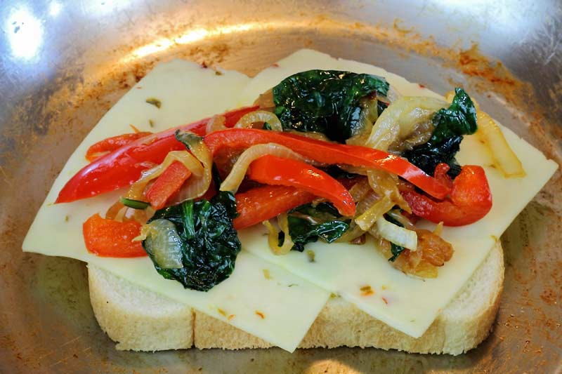 Assembly of grilled cheese pepper jack roasted red pepper caramelized onion spinach
