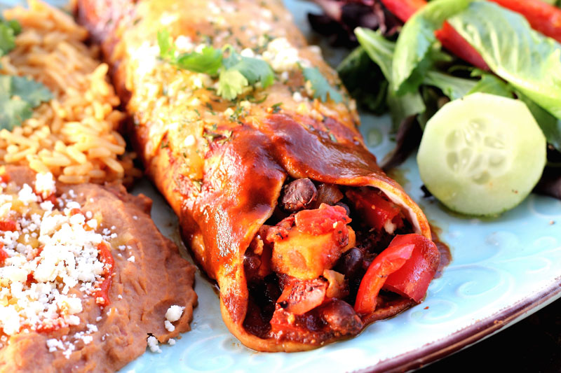 Vegetarian enchiladas plated with rice beans and salad