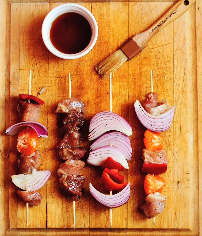 Assembled pork loin skewers with basting brush and brandy glaze