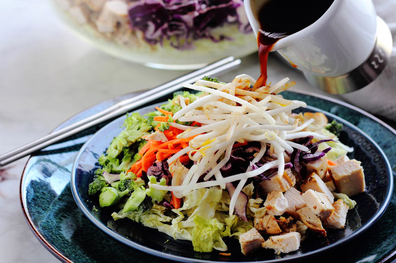 Pouring salad dressing onto Chinese chopped chicken salad