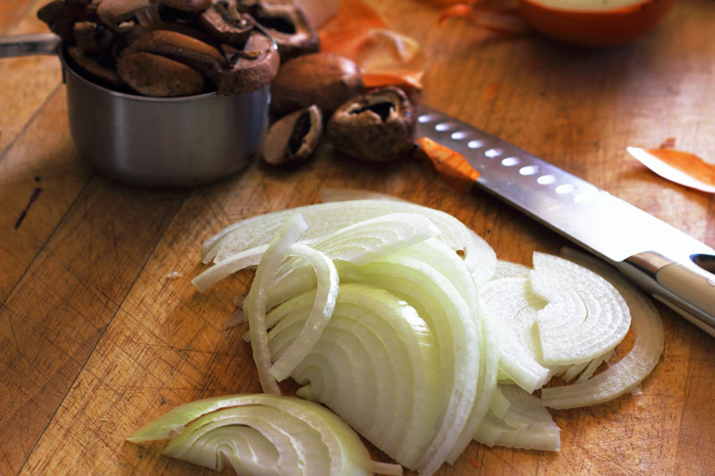sliced onions and portobello mushrooms ready to cook sausage and artichoke