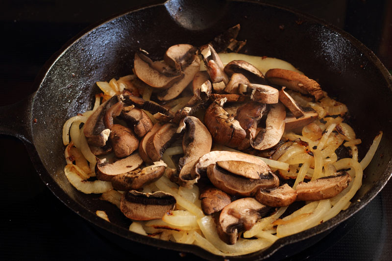 sausage and artichoke caramelized onions with portobello mushrooms in cast iron skillet