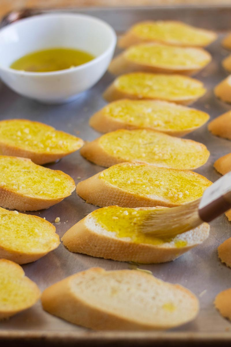 tray of baguette sliced bread with brush to glaze olive oil and garlic