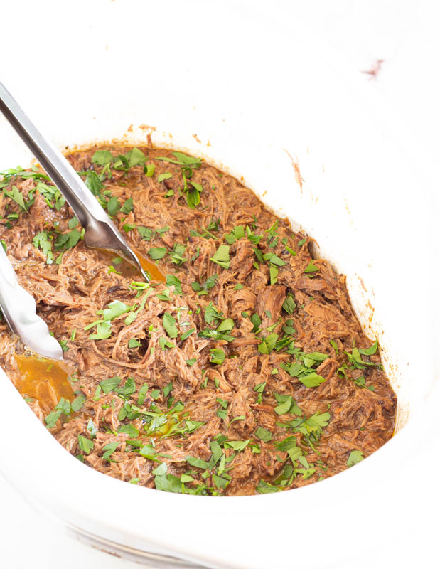 slow cooker barbacoa in crock pot with cilantro and spices